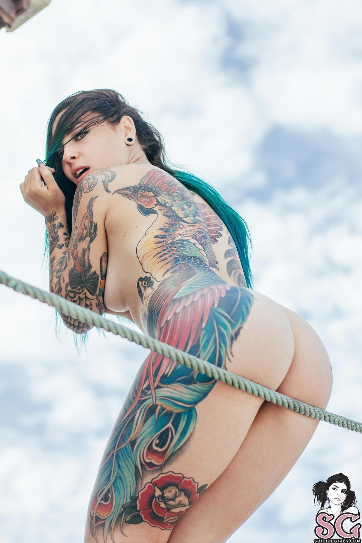 A heavily tattooed girl posing nude